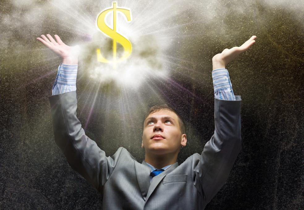 Businessman praying at dollar sign above